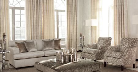 Kobe -  Paladio Fabric Collection - Cream curtains, an off-white sofa, 2 grey and white patterned armchairs, a large padded footrest, and metallic cushions