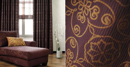 Kobe -  Paladio Fabric Collection - Aubergine and rich gold coloured swirling florals and patterns covering a chaise longue, a scatter cushion and curtains