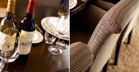 Kobe -  Pearls Fabric Collection - A wooden table with glasses, crockery, bottles of wine, and dining chairs covered with subtly patterned light brown fabric