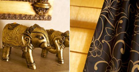 Kobe -  Pearls Fabric Collection - Two gold carved elephant sculptures with folds of black fabric patterned with pretty dark brown coloured florals