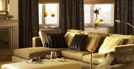 Kobe -  Pearls Fabric Collection - Very dark brown curtains with a luxurious gold corner sofa, a rectangular padded footstool, and black and gold cushions