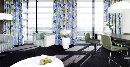 Kobe -  Peru Fabric Collection - Light shades of blue and green making up floral curtains, striped armchairs, with a black table, and grey and metal chairs