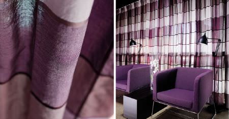 Kobe -  Peru Fabric Collection - 2 bright purple armchairs with silver metal frames, and sheer curtains made with horizontal stripes in 3 shades of purple