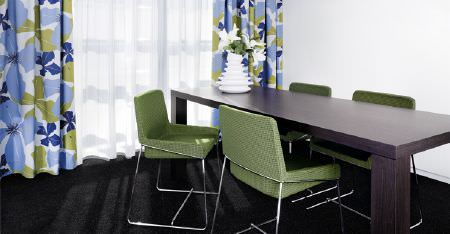 Kobe -  Peru Fabric Collection - A dark purple table with 4 green metal framed chairs, sheer white curtains and blue, white and green floral curtains