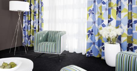 Kobe -  Peru Fabric Collection - Blue, white and green fabrics making up floral curtains, striped armchairs, with a white table, a lamp, and a large vase