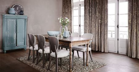 Kobe -  Poetry Fabric Collection - A fluffy rug, blue cupboard, light purple curtains, a wooden table, six plain white chairs, a glass vase, a bowl and a jug