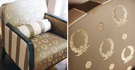 Kobe -  Royal Astoria Fabric Collection - Cream and pale brown fabrics featuring simple stripes and wreath patterns, covering a wood framed armchair, with a cuhsion