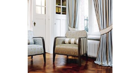 Kobe -  Royal Astoria Fabric Collection - Light shades of blue and brown making up striped curtains, cushions and wood framed armchairs with wreath patterns and stripes
