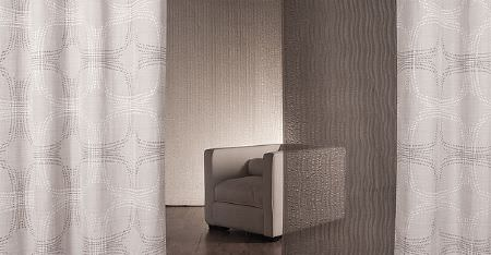 Kobe -  Sensu CS Fabric Collection - A white cube shaped armchair with subtly patterned curtains in white and very pale grey, with sheer black panels