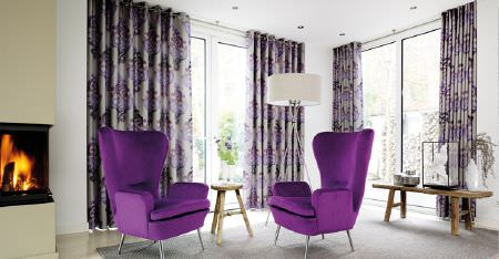 Kobe -  Sindara Fabric Collection - Two modern, bright purple armchairs, purple and grey patterned curtains, a fire, two wood tables and a white lampshade