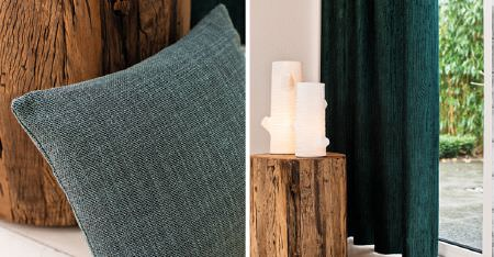 Kobe -  Sindara Fabric Collection - Two cream pillar candles on a table made from a tree stump, with a plain dark teal cushion and a matching curtain