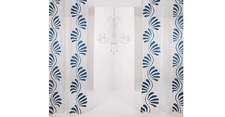 Kobe -  Skimo Fabric Collection - A white chandelier with two white curtains which feature deep turquoise coloured patterns