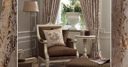 Kobe -  Tournelle Fabric Collection - Metallic gold patterns on light grey curtains, with a cream wood framed armchair with a brown seat and back, and a cushion