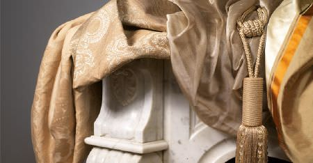 Kobe -  Tournelle Fabric Collection - Luxurious plain, striped and patterned coffee coloured fabrics with a tassel, draped over carved white wood furniture