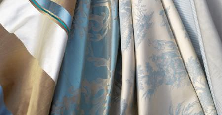 Kobe -  Tournelle Fabric Collection - Swathes of brown, white and blue fabric, luxurious light blue and silver patterned fabric, and blue and white floral fabric