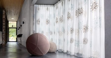 Kobe -  Villa Fabric Collection - Large beige and pale pink sphered beside sheer white curtains made with large, stylised florals in brown and silver