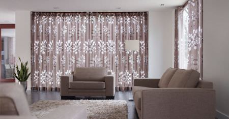 Kobe -  Villa Fabric Collection - Light brown and white patterned curtains with a plain coffee coloured sofa and armchair, a fluffy cream rug and a white lamp