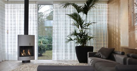 Kobe -  Villa Fabric Collection - A large dark grey corner sofa, sheer white horizontally striped curtains, an oversized black flower pot and a fluffy rug