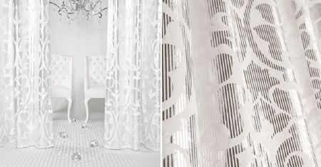 Kobe -  White Fabric Collection - A silver chandelier and two white chairs, behind two white curtains featuring glamorous metallic silver patterns
