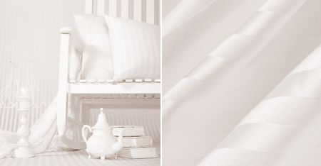 Kobe -  White Fabric Collection - Folds of white fabric with lustrous and matt stripes, and a white chair, cushions, books, candlesticks and a teapot