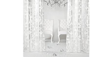 Kobe -  White Fabric Collection - Glamorous white and metallic silver patterned curtains hanging in front of white padded armchairs and a silver chandelier