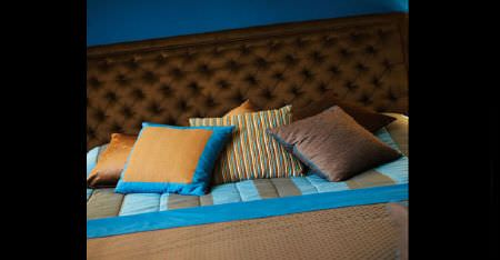 Kobe -  Zaffiro CS Fabric Collection - A large bed with a padded headboard, bedding and scatter cushions, all made in chocolate brown and aqua blue fabrics
