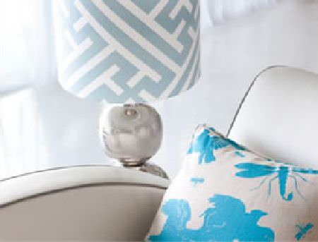 Korla -  Korla Fabric Collection - A silver lamp with a baby blue and white patterned shade, a plain white, curved sofa, with an aqua blue and white cushion