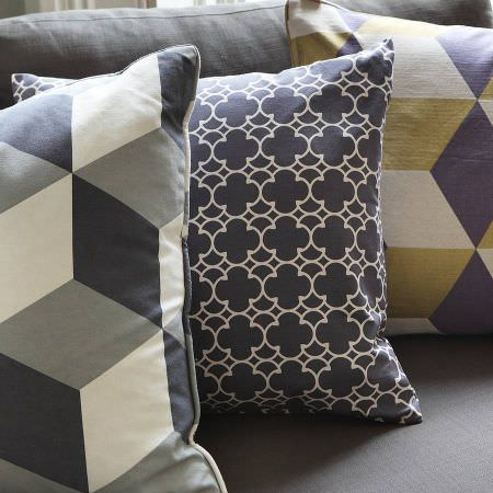 Korla -  Korla Fabric Collection - A dark grey sofa with three geometric print cushions made in colours such as white, black, grey, gold and purple