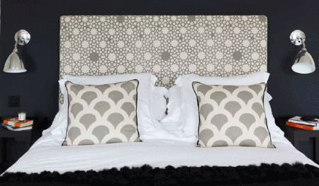 Korla -  Korla Fabric Collection - A bed with white bedding, a fluffy black throw, grey and white scalloped cushions and a geometric print headboard, and 2 lamps