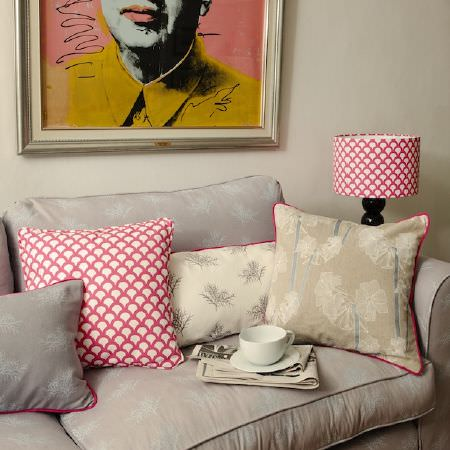 Korla -  Korla Fabric Collection - A light grey sofa with plain and patterned red, white,light grey and beige cushions, by a black lamp with a scalloped shade