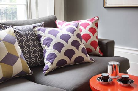 Korla -  Korla Fabric Collection - Dark grey, white, green-gold and red geometric and scallop print cushions, on a dark grey sofa, with a small round red table