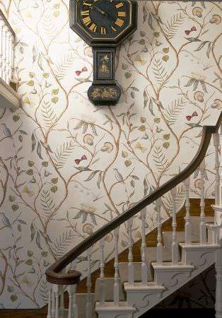 Lewis and Wood -  Lewis And Wood Fabric Collection - A white and dark wood staircase with an antique black and gold wall clock, withwhite, brown, grey and green patterned walls