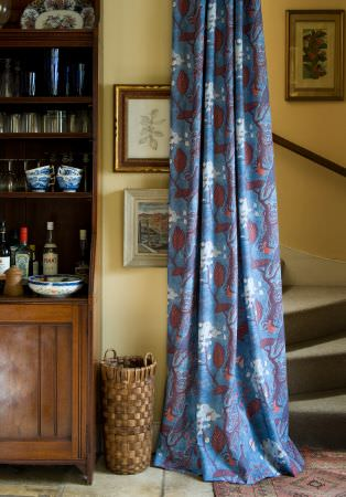 Lewis and Wood -  Lewis And Wood Fabric Collection - A large wood dresser with a wicker basket, blue, red and white patterned curtains, glasses, crockery and framed pictures