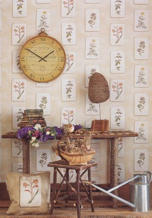 Lewis and Wood -  Lewis And Wood Fabric Collection - A vintage style clock on floral patterned wallpaper with a matching cushion, a wooden bench and stool, and a watering can