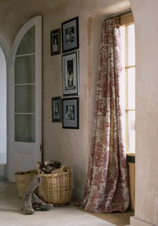 Lewis and Wood -  Lewis And Wood Fabric Collection - Wicker baskets, boots and framed pictures beside floor-length curtains featuring red and whitefloral patterns