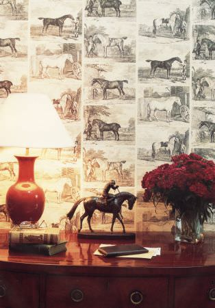 Lewis and Wood -  Lewis And Wood Fabric Collection - A red wood side board with grey and white horse print wallpaper,a red and white lamp, a horse statue and a glass vase