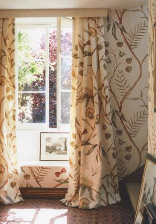 Lewis and Wood -  Lewis And Wood Fabric Collection - A large leaf and bird pattern covering cream curtains and wallpaper in shades of brown and green, with a framed picture