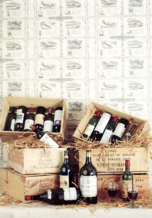 Lewis and Wood -  Lewis And Wood Fabric Collection - Wooden boxes and crates filled with straw and wine bottles, in front of patterned wallpaper made in light grey and white