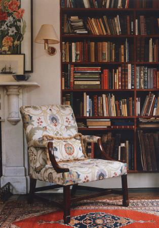 Lewis and Wood -  Lewis And Wood Fabric Collection - A bright patterned rug in front of a large bookcase with a cream, red, blue and grey padded armchair with wooden legs