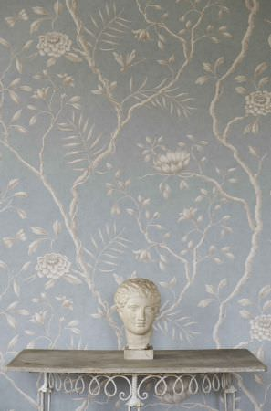 Lewis and Wood -  Lewis And Wood Fabric Collection - A white bust on a simple grey-white table, in front of a floral and branch patterned backdrop made in pale blue and cream