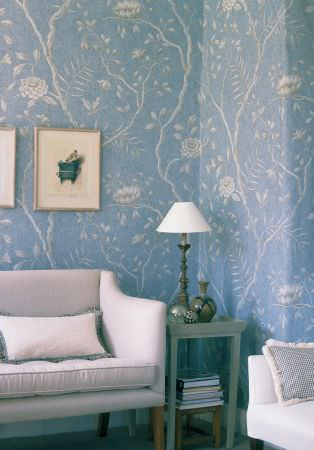 Lewis and Wood -  Lewis And Wood Fabric Collection - White flowers and branches printed on cobalt blue wallpaper, withwhite sofas, a small grey-green table and a white lamp
