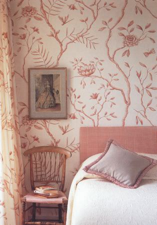 Lewis and Wood -  Lewis And Wood Fabric Collection - A salmon pink headboard, white bedding, patterned wallpaper, a grey cushion, a wooden chair with pink seat, and a picture