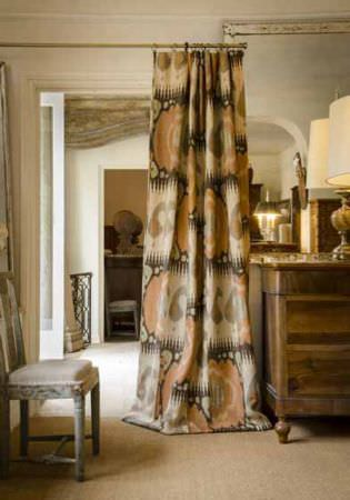 Lewis and Wood -  Lewis And Wood Fabric Collection - An apricot, cream, grey and beige patterned curtain, beside a grey chair, a large dresser, gold vases and a huge lamp