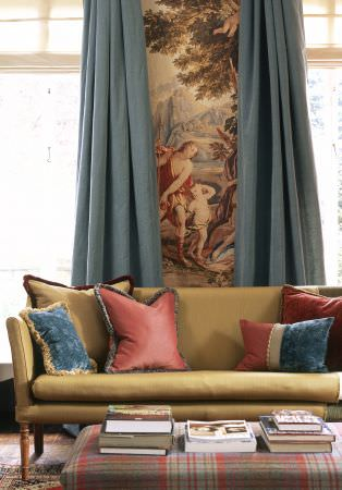 Lewis and Wood -  Lewis And Wood Fabric Collection - A gold sofa with plain, fringed gold, red and blue scatter cushions, plain blue curtains and a red and grey tartan ottoman