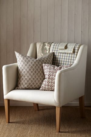 Lewis and Wood -  Lewis And Wood Fabric Collection - Simple white armchair with wooden legs, with scatter cushions and draped with fabric, allwith red, grey and green patterns