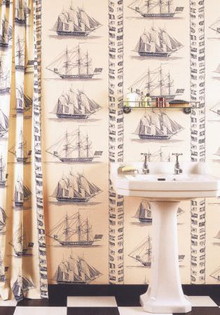 Lewis and Wood -  Lewis And Wood Fabric Collection - Blue-grey sailboats and flags printed on cream coloured curtains and wallpaper behind a white sink, with a glass shelf