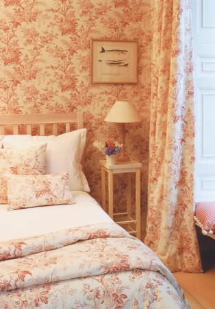 Lewis and Wood -  Lewis And Wood Fabric Collection - Red and cream floral patterned wallpaper, curtains, cushions and throws, with a white bed and bedding, a white table and a lamp