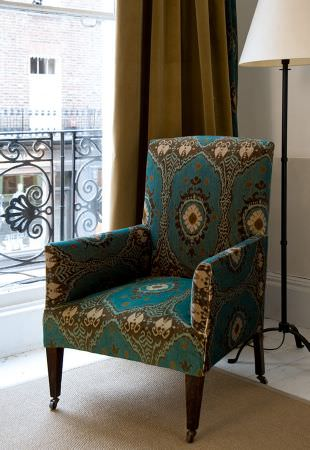Lewis and Wood -  Lewis And Wood Fabric Collection - An armchair patterned in turquoise, cream and brown-grey, with wooden legs, khaki curtains and a lamp with a cream shade