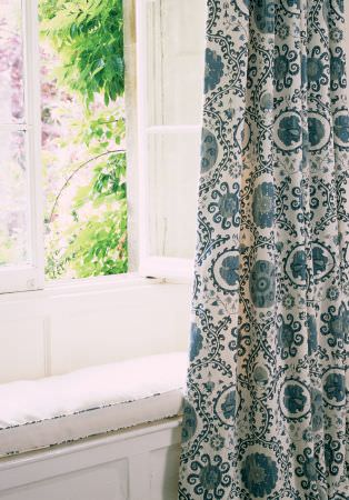 Lewis and Wood -  Lewis And Wood Fabric Collection - A white padded window seat hidden by long curtains made with a repeated white and marine blue coloured swirling pattern