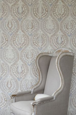Lewis and Wood -  Lewis And Wood Fabric Collection - A plain light grey and white wood framed padded armchair in front of a pale grey, beige and off-white patterned backdrop